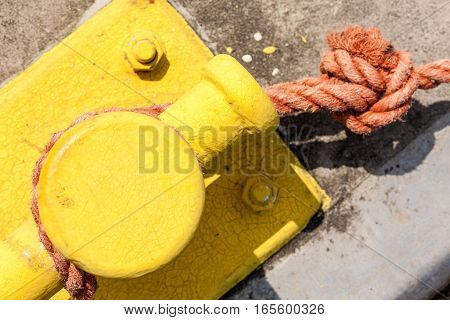 Shipping objects concept. Sailing ropes tied around yellow marina pins. Outdoor shot on sunny day.