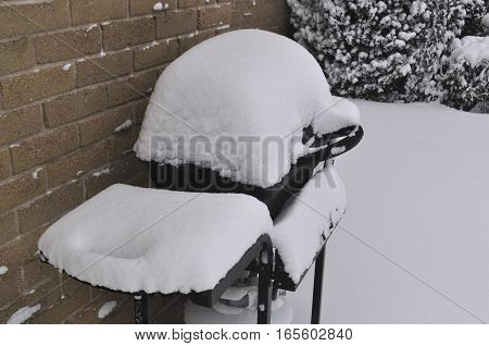 Winter scene - Barbeque covered in snow by the wall of a residential house somewhere in Canada
