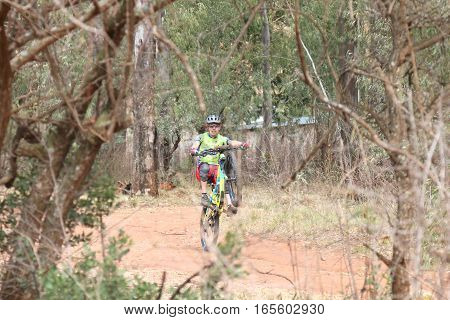 Young Man Showing Off By Popping Wheelie At Mountain Bike Race