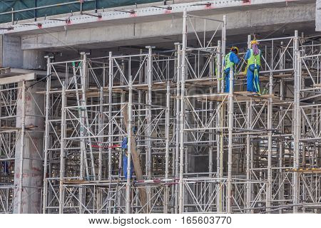 Construction site with team of construction laborers working on scaffold.