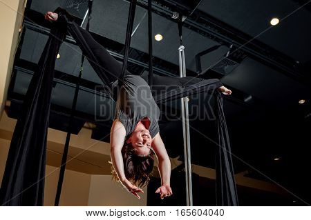 An average looking girl upside down in a butterfly aerial pose. She is hanging from silks anchored into a ceiling.