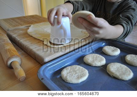 A small boy cooking - cutting out round shapes from a rolled-out yeast dough