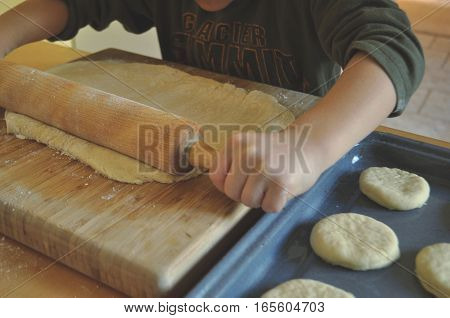 A boy kneads and cuts out cookies from a dough on a wooden board with dad supervising