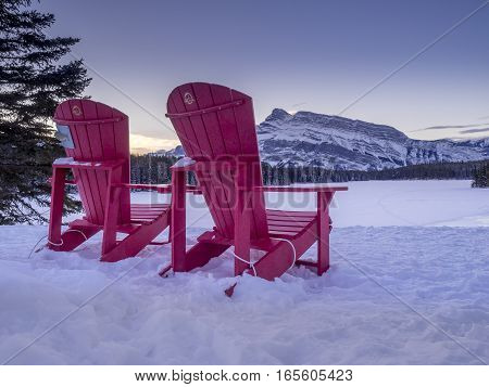 BANFF, ALBERTA - JAN 15: Red Chairs at Two_jack Lake with Parks Canada logos on January 15, 2017 iin Banff National Park, Alberta, Canada. Rundle Mountain is in the background.