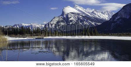 Mount Rundle reflected in the icy waters of Vermillion Lakes near Banff Alberta Canada