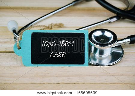 Wooden tag written with Long-Term Care and stethoscope on wooden background. Medical and Healthcare concept.