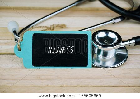 Wooden tag written with Illness and stethoscope on wooden background. Medical and Healthcare concept.