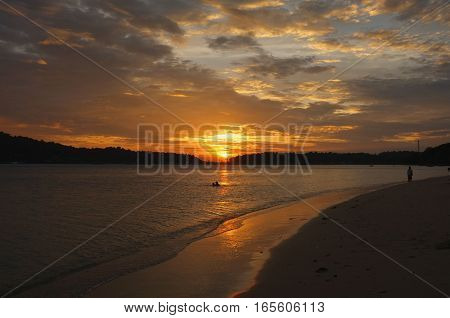 Silhouette couple  in the sea with a beautiful sunset in background