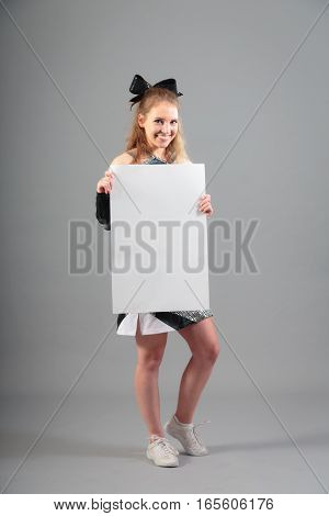 young cheerleader on gray background, holding white poster