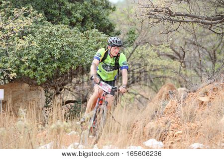 Middle Aged Male Riding Through Bush At Mountain Bike Race