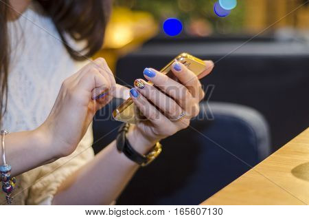 Girl sitting in restaurant with phone in hands