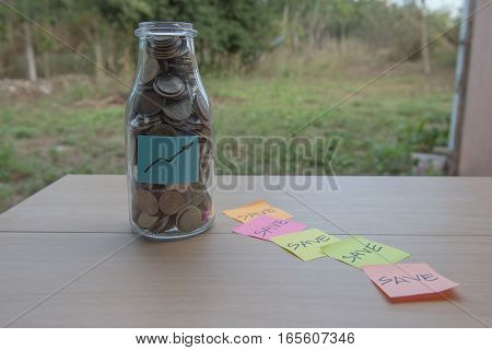 graph Writing in the paper, Coins in a glass jar, concept Saving Money  step with deposit coin in bank stack growing business.