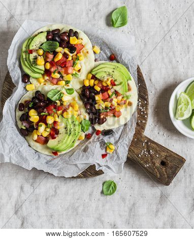 Spicy bean tacos with corn salsa and avocado on a rustic cutting board on a dark background. Delicious vegetarian snack