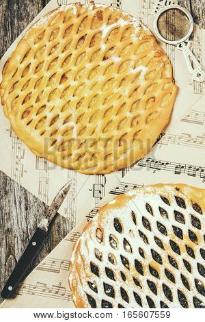 Homemade apple pie, plum pie on shabby wooden background and craft paper with a print of musical notes. Selective focus. Toned image in vintage style. Top view