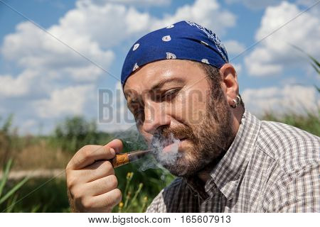 Bearded man having rest with his pipe outside on a summer day