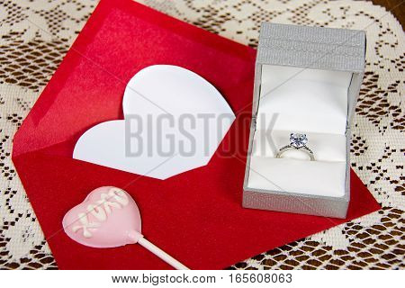 diamond ring in box with pink valentine sucker on red envelope