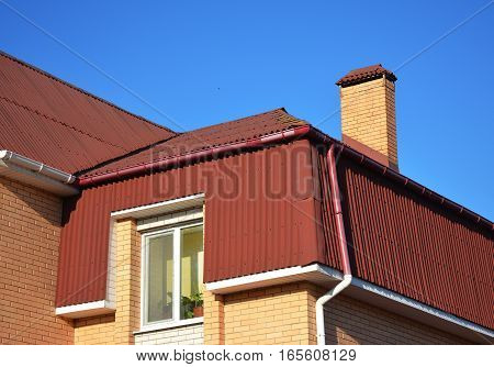 Mansard house roofing type. Attic roof exterior with asphalt shingles and plastic rain gutter system.