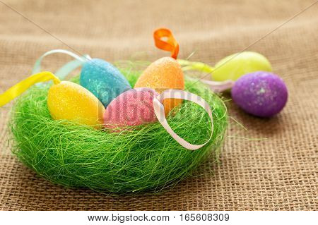 Easter eggs in the decorative nest. Easter still life with colored eggs.