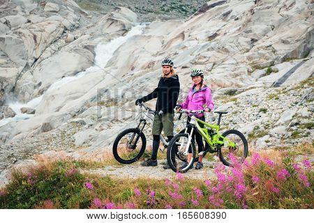 Young Couple Cycling. Shot taken in Switzerland, near Rhone Glacier and Furka Pass.