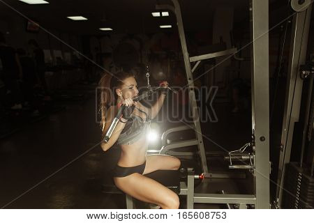 Attractive Young Woman Doing Exercise For Back On Lat Machine.