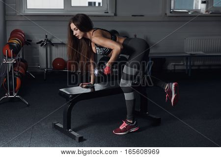Fitness Girl Execute Exercise With Dumbbells, On Broadest Muscle Of Back.