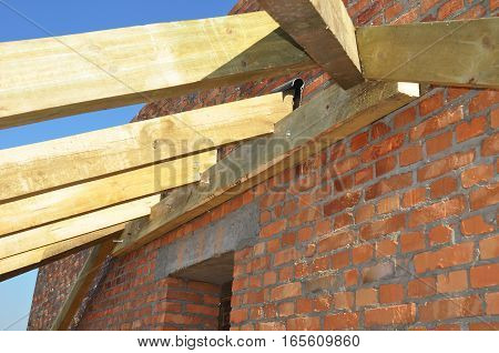 Roof trusses. Close up on installation of wooden beams at construction the roof truss system of the house. Roofing Construction. Building Attic Interior.