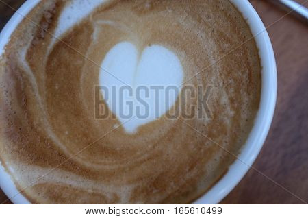 Hot white coffee cup with heart shape latte art on wooden table