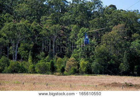 blue helicopter flies over the field and forest, aerial