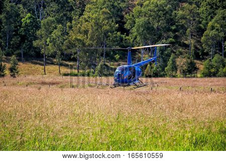 blue helicopter flies over the field, aerial