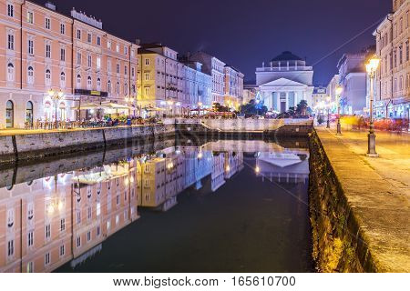 Trieste - December 2016, Italy: Night view of the main landmark in the city - Grand Canal historical buildings mirror reflected in the water. Popular tourist destination in Northern Italy