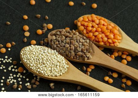 Three wood spoon with quinoa lentil and buckwheat on black background