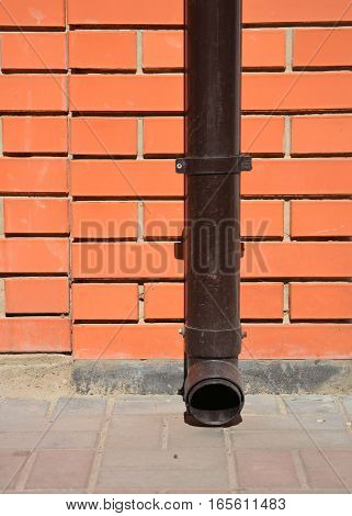 House rain gutter downspout with wall holder without water drainage on the pavement
