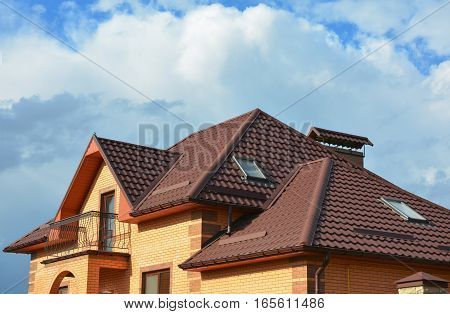 New roofing construction with attic skylights rain gutter system roof windows and roof protection from snow board snow guard house exterior. Modern House Roofing Construction.