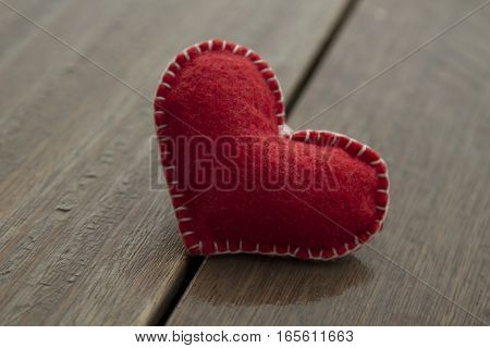 Red textile heart on wood background love concept