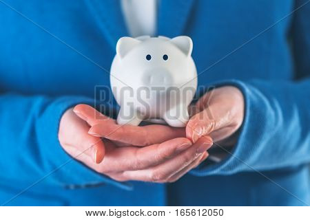 Businesswoman with piggy coin bank concept of budget planning saving and investing