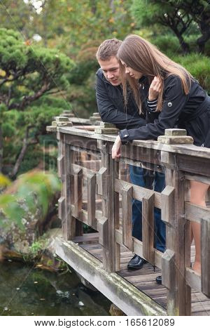Young romantic couple - good-looking man and attractive woman - standing on the bridge in japanese garden talking and looking on the water.