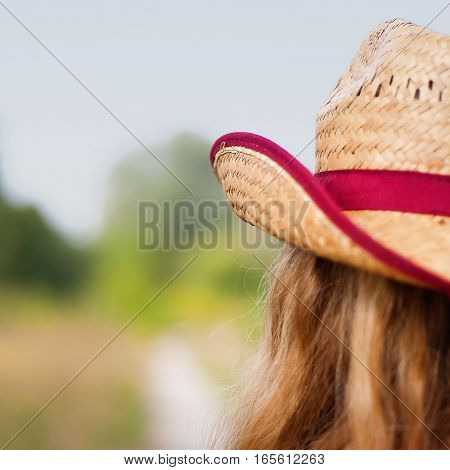 Girl's head in a hat from the back walking on a non-urban road unfocused