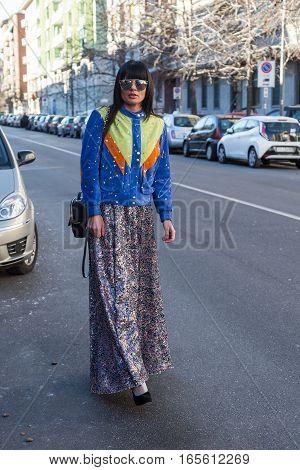 MILAN ITALY - JANUARY 16: Fashionable woman poses outside Etro fashion show building during Milan Men's Fashion Week on JANUARY 16 2017 in Milan.