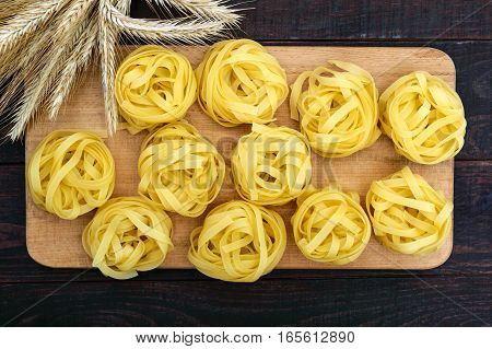Pasta tagliatelle in the form of nests on a cutting board on a dark wooden background with spikelets of wheat. The top view.