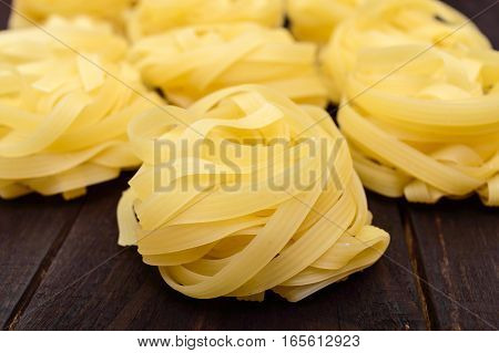 Pasta tagliatelle in the form of nests onthe dark background. Close-up.