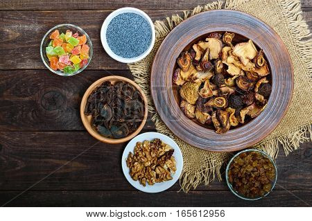 Dried fruit (apples pears apricot) berries walnut kernels raisins poppy seeds in a bowl on dark wooden background. The top view. The ingredients for the porridge.