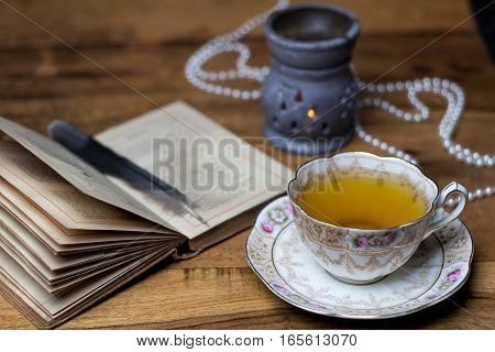 Open Old Book On The Wooden Desk, Porcelain Cup Of Tea And Saucer, Aroma Lamp, Candle, Pearls, Feath