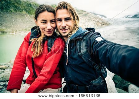 Young Couple Hiking in the Swiss Alps, Taking a Selfie.