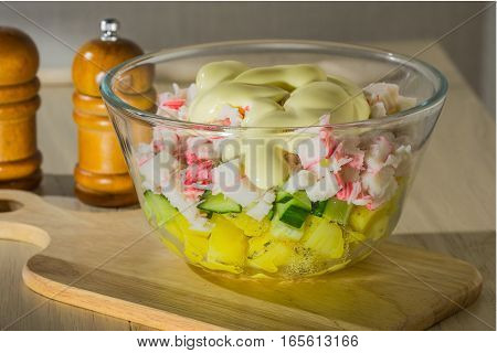 Salad of crab sticks potato cucumber with mayonnaise in a transparent bowl