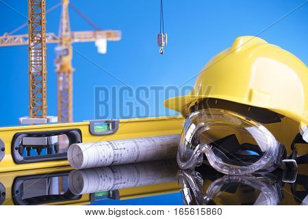 Workplace of architect. Rolls with building projects, equipment of architect: crash helmet and spirit level on glass table.