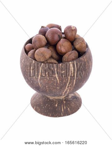 roasted chestnuts in coconut shell cup on white background