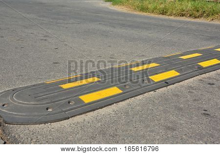 Traffic safety speed bump on an asphalt road. Speed bumps (or speed breakers) are the common name for a family of traffic calming devices.