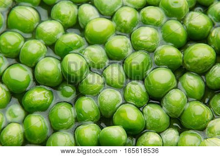 Wet fresh green peas in water closeup as background. Healthy vitamin food.