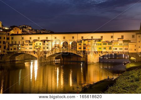 Famous Ponte Vecchio bridge over the Arno river in Florence Italy lit up at night