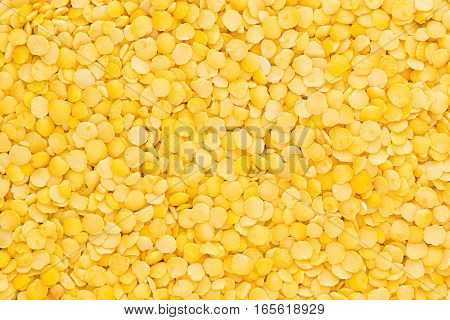 Yellow purified lentil closeup top view background. Healthy protein food.